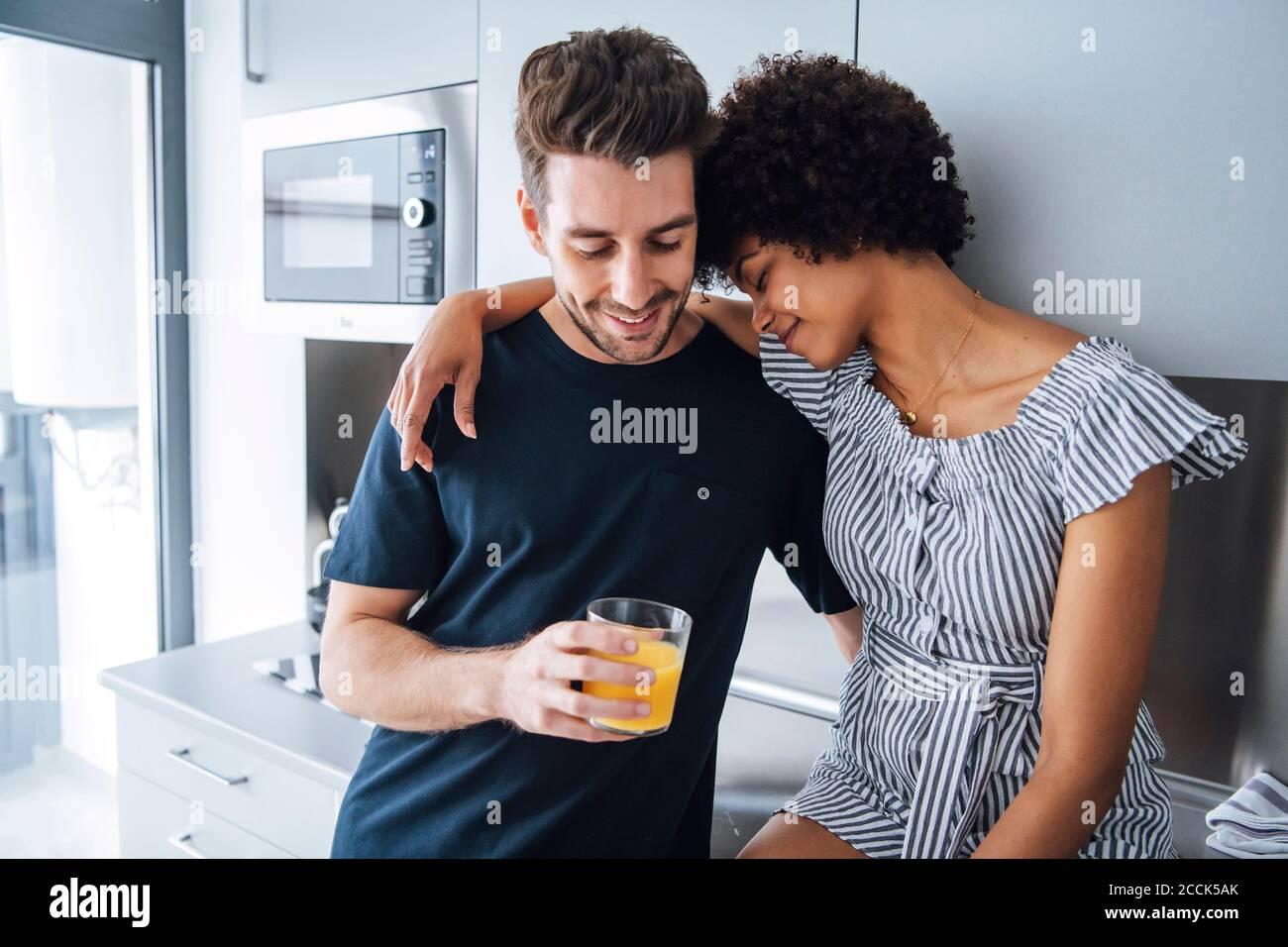 Pareja multiétnica romántica en la cocina del ático Foto de stock