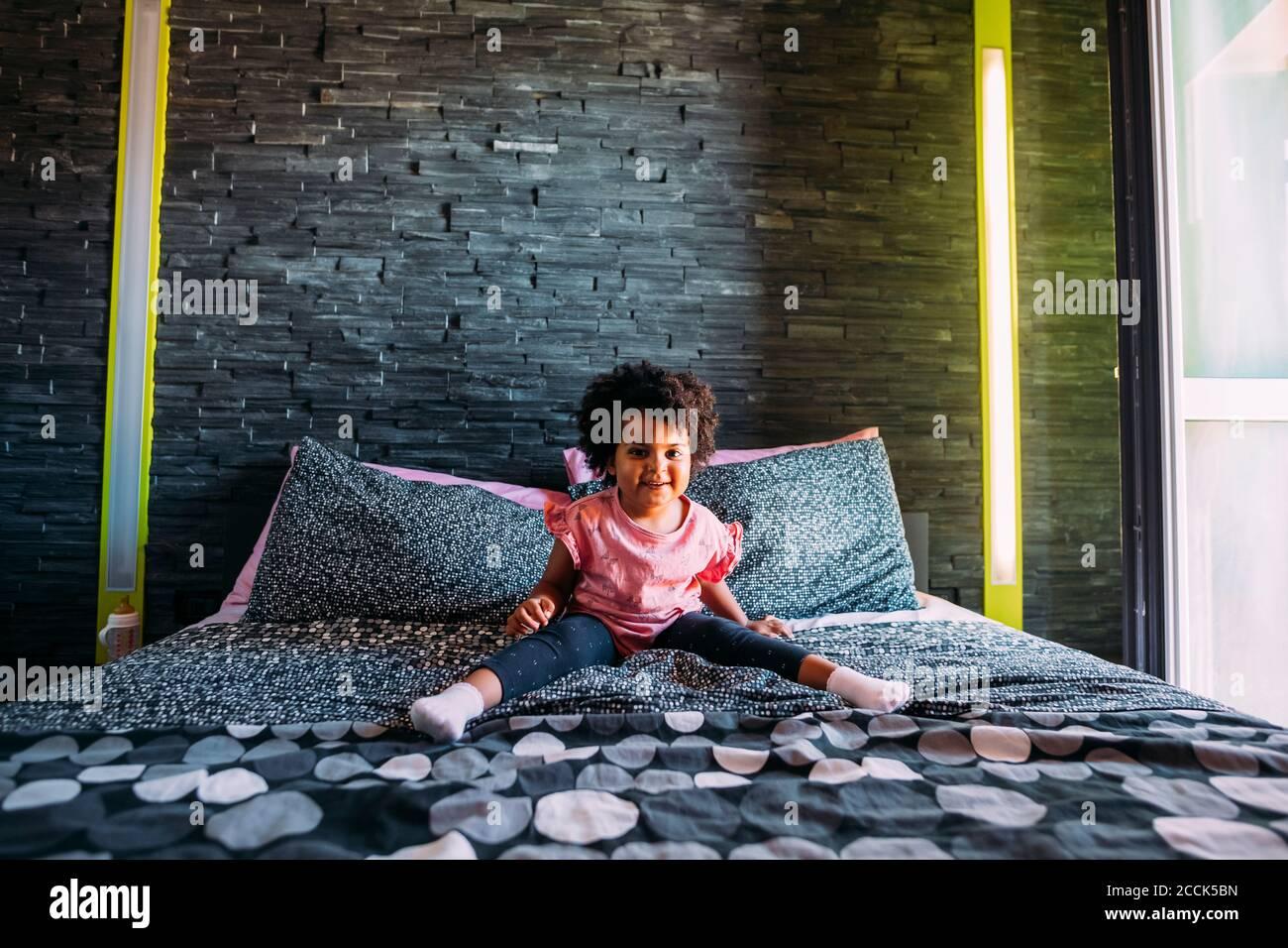 Niña sonriente con las piernas separadas sentadas en la cama contra pared en casa Foto de stock