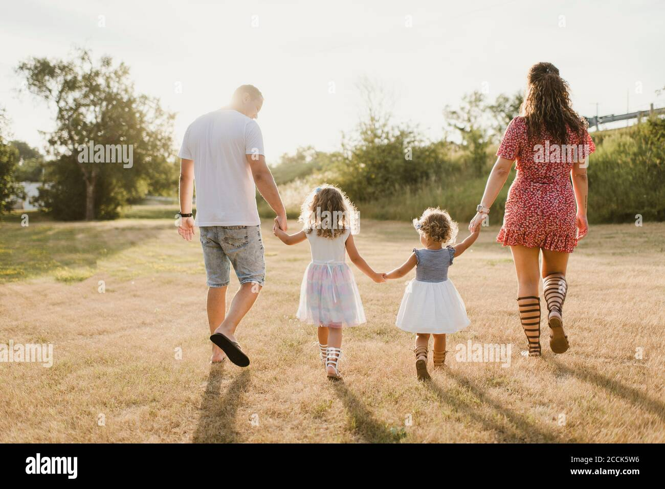 Familia caminando en un prado a contraluz Foto de stock
