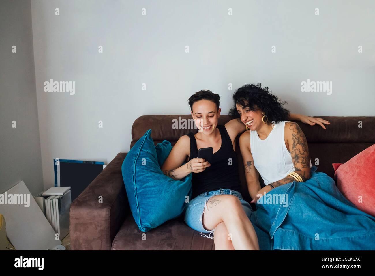Alegre pareja usando el teléfono mientras se sienta en el sofá Foto de stock