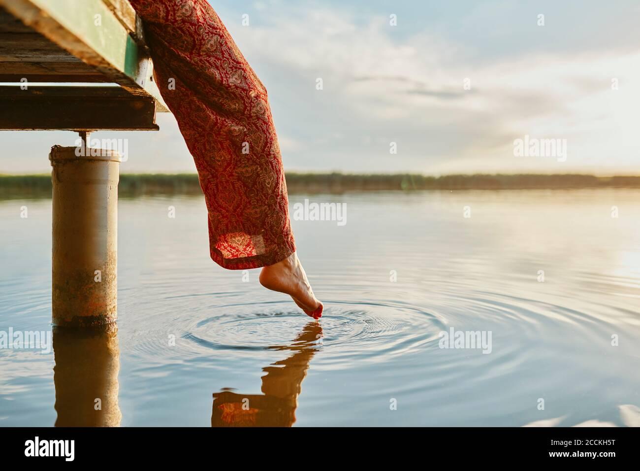 Mujer sentada en el embarcadero en un lago al atardecer tocando el agua con su pie Foto de stock