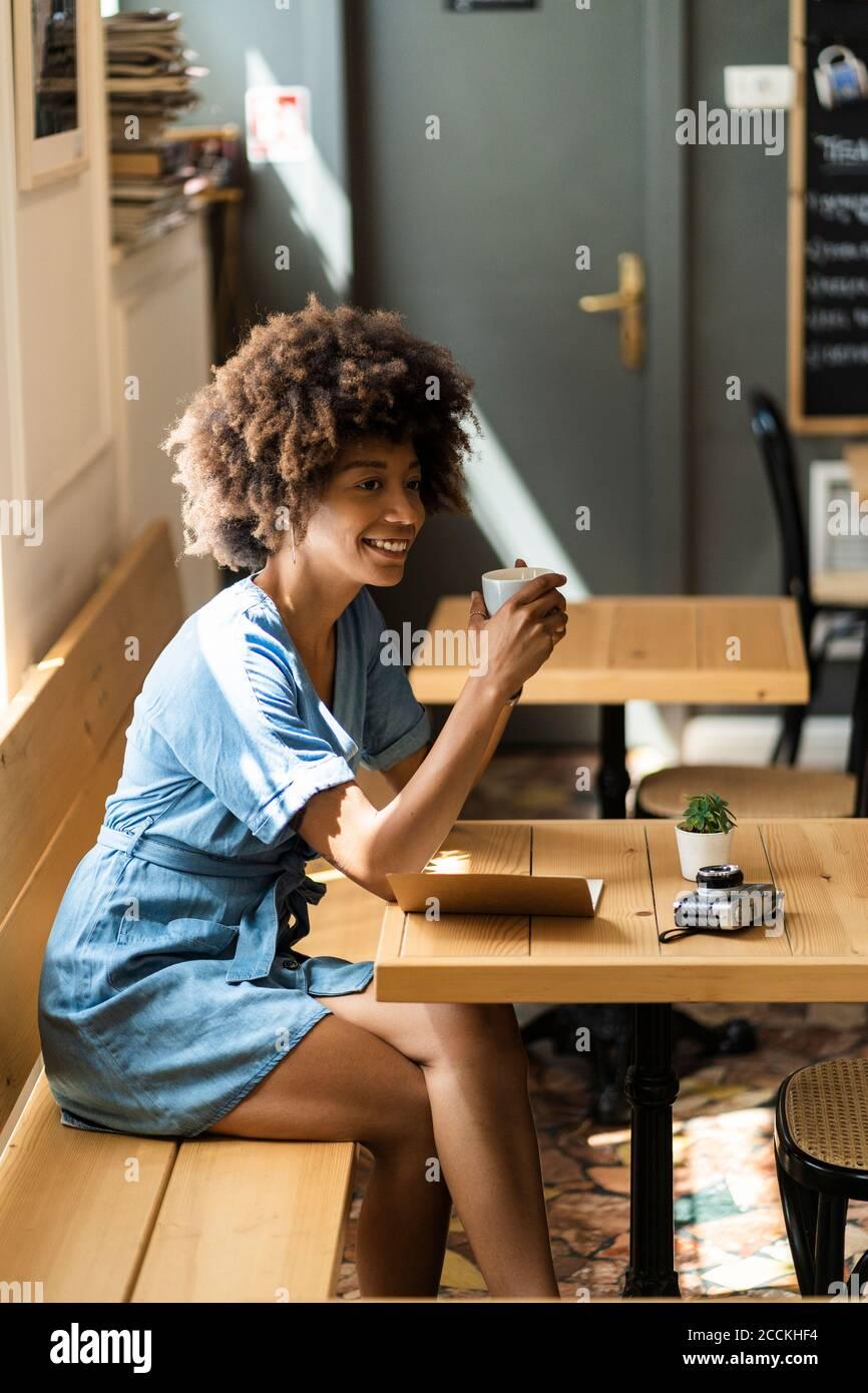 Una mujer pensativa sosteniendo una taza de café mientras se sentaba en la mesa café Foto de stock