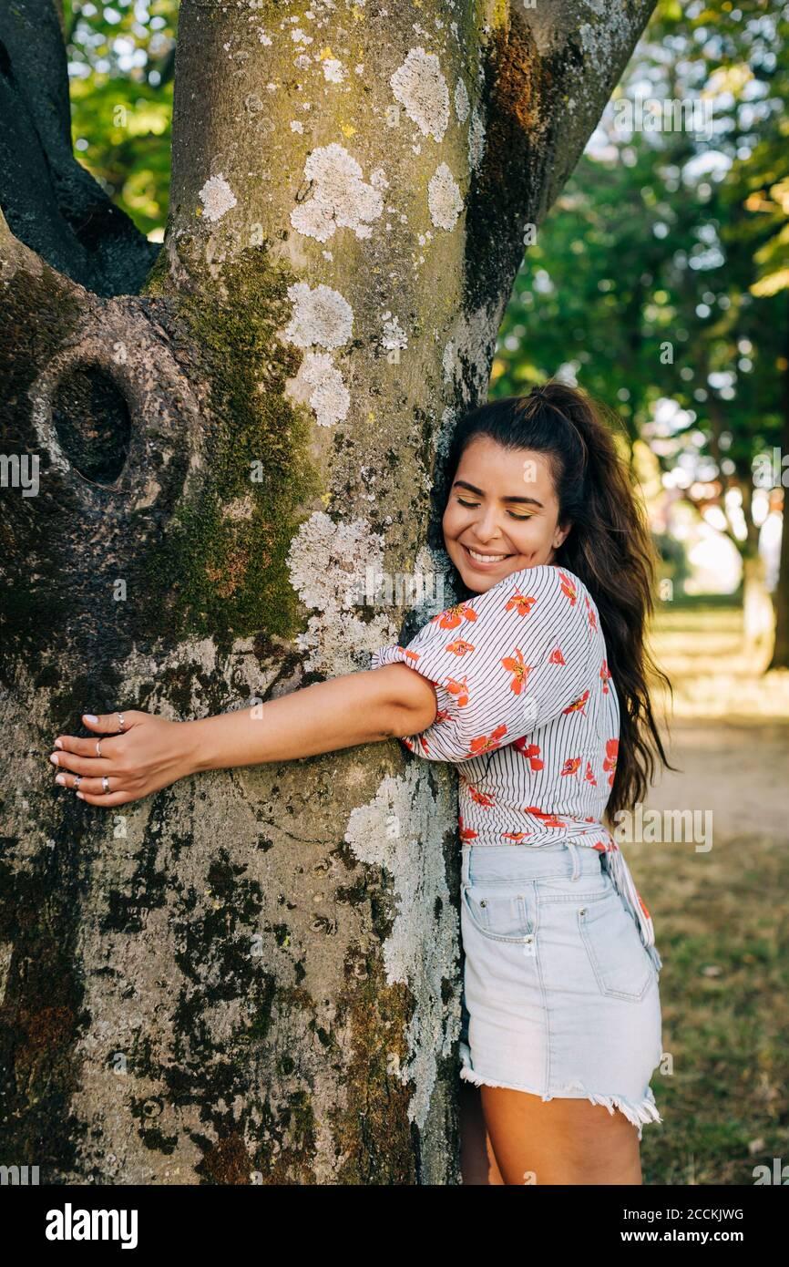 Sonriente joven con los ojos cerrados abrazando el tronco del árbol mientras de pie en el parque Foto de stock