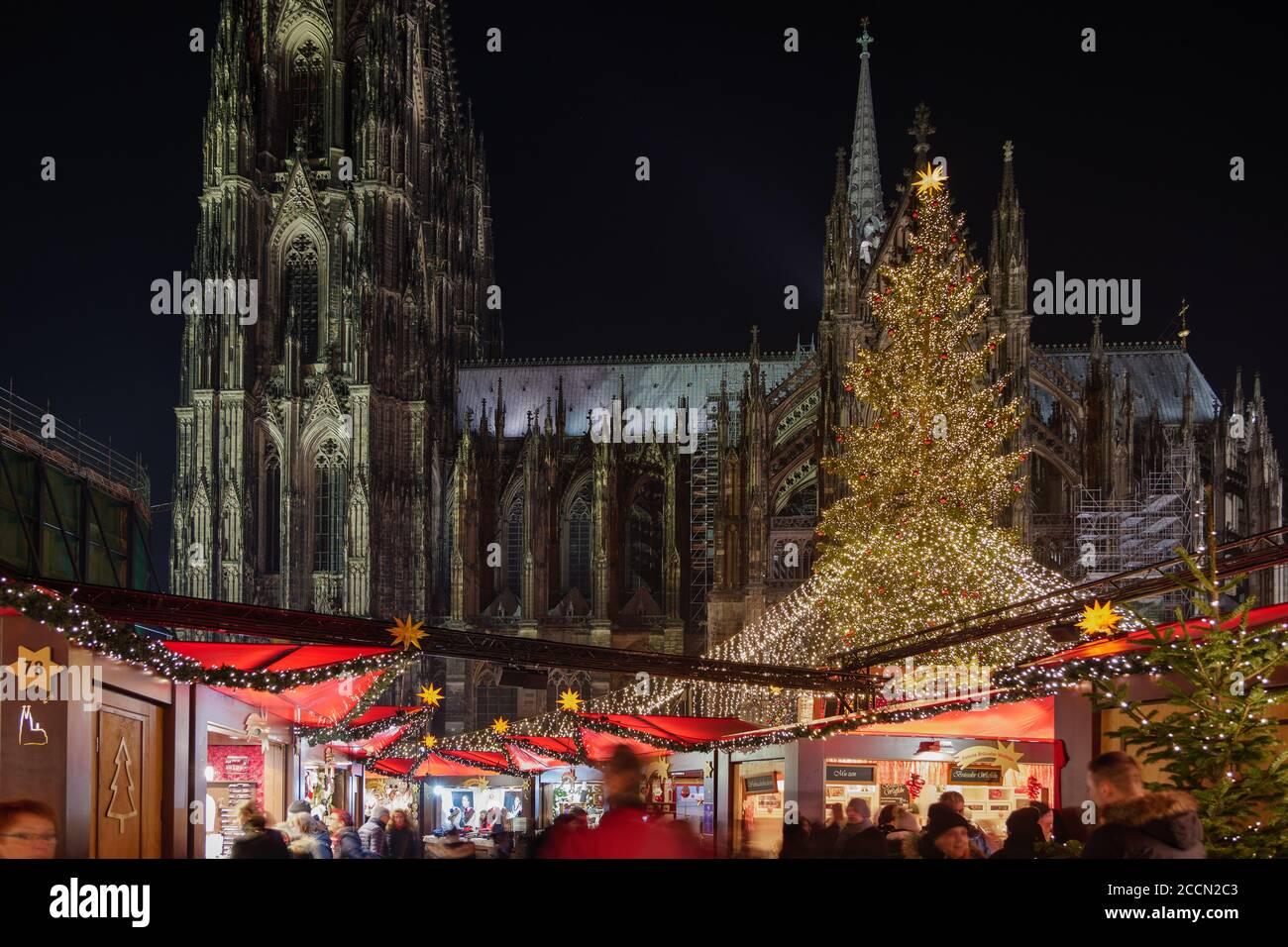Paisaje nocturno, Weihnachtsmarkt, mercado de Navidad en Colonia, con varios puestos iluminados decorados frente al árbol de Navidad y la Catedral de Colonia. Foto de stock
