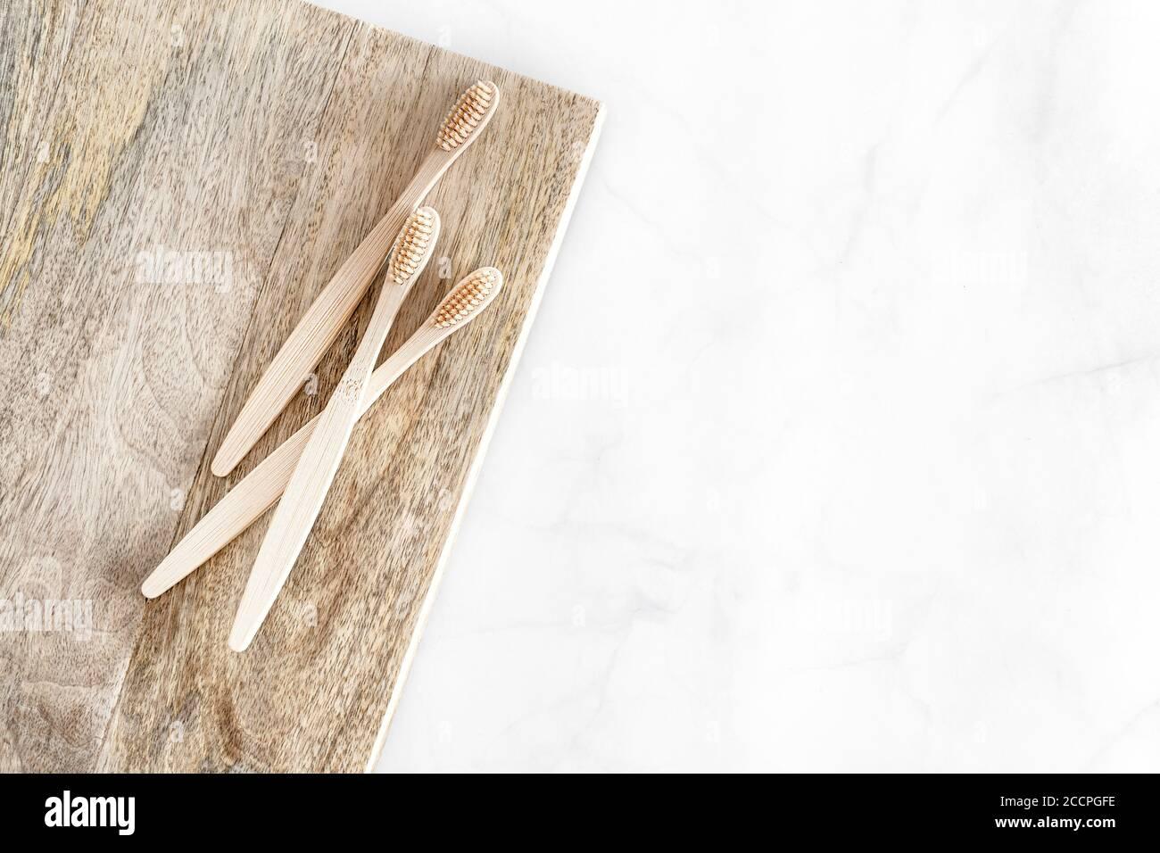 Composición con cepillos de dientes de bambú biodegradables sobre fondo de mármol. Sostenible, sin residuos, sin plástico, concepto de estilo de vida. Accesorios de higiene bucal ecológicos.Lay plano, vista superior, espacio de copia. Foto de stock