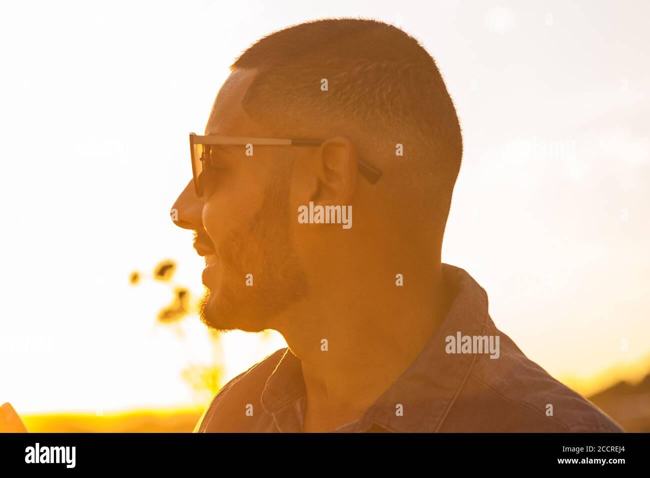 Feliz hombre latino caminando y disfrutando de la puesta de sol con una vista natural del paisaje. Luz natural cálida. Foto de stock