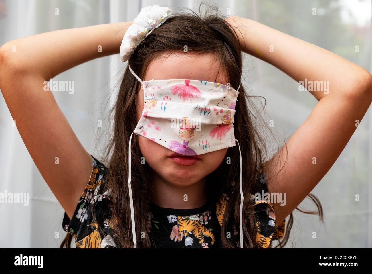 Niña que intenta en la cubierta casera de la cara durante el Covid-19 pandemia Foto de stock