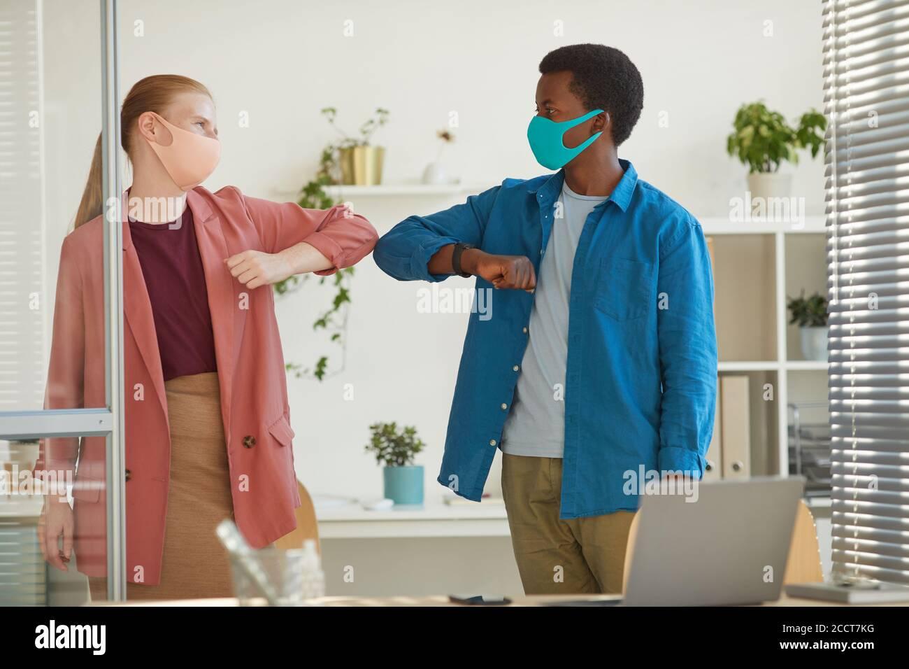 Retrato de una mujer joven con mascarilla golpeando los codos con afro-americana colega como saludo sin contacto mientras trabaja en la oficina post pandémica Foto de stock
