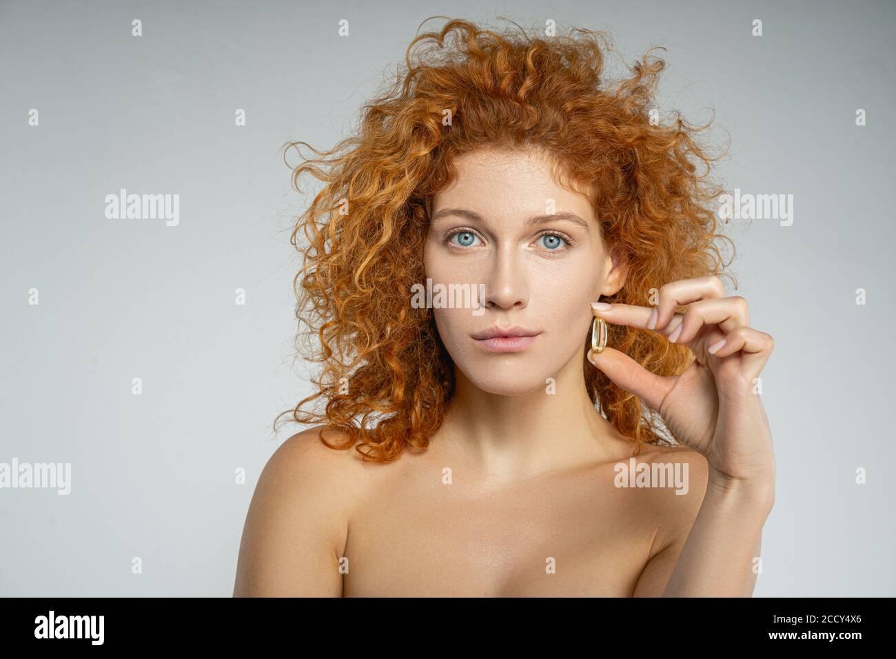 Mujer sosteniendo una cápsula en una mano Foto de stock