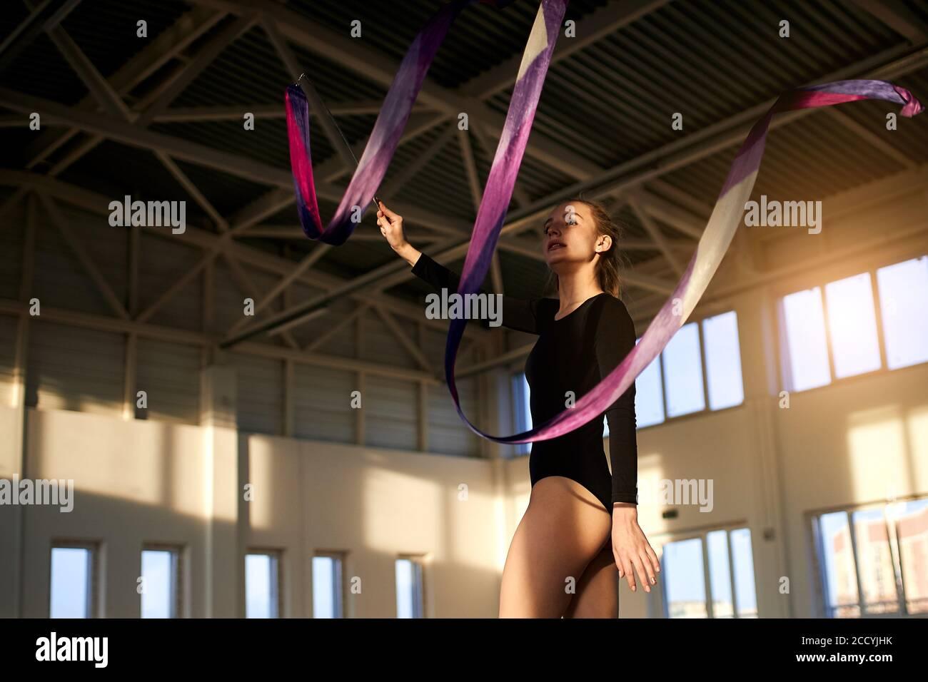 Profesional talentoso femenino de arte gimnasta agitando la mano con cinta violeta, trabajando en estudio brillante, tiro inferior, concepto de estilo de vida saludable Foto de stock