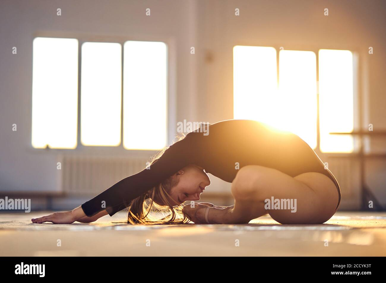 Retrato de una joven deportiva sentada en el suelo, inclinándose hacia delante, estirándose en el salón deportivo, en la puerta, concepto deportivo profesional Foto de stock