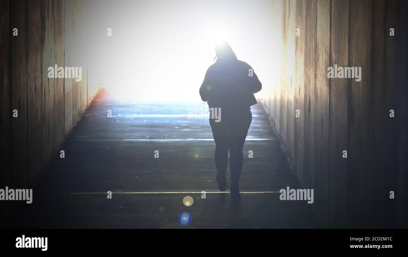 Una imagen muy saturada de una sola mujer que se desvanece caminando a una luz brillante al final de un túnel. Muerte, morir, suicidio, fin de la vida ellos Foto de stock