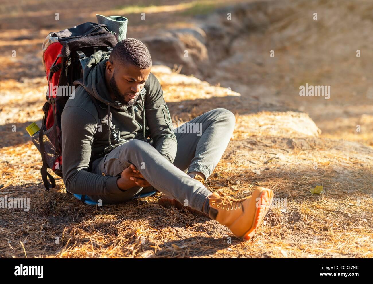 Hombre negro sentado en el suelo, frotándose la rodilla Foto de stock