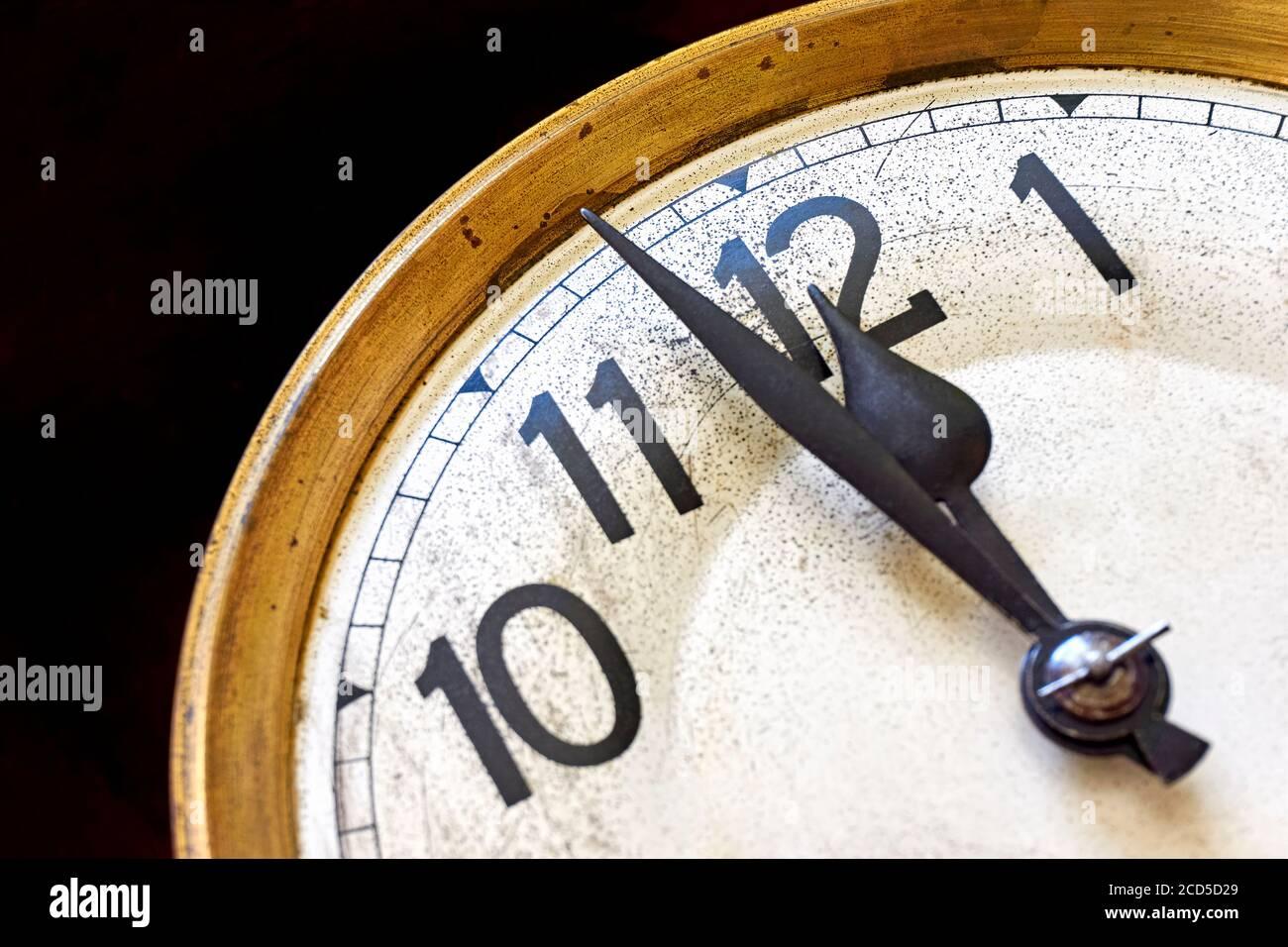 Antiguo reloj vintage muestra de 2 minutos a 12 en punto contra un fondo negro. Concepto de fin de año o cuenta atrás. Foto de stock