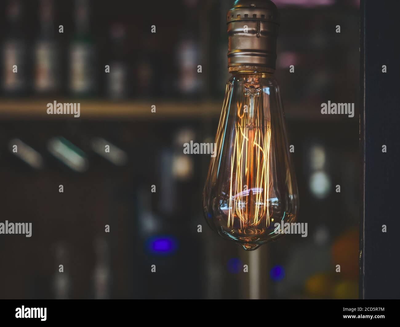Lámpara transparente con mecha naranja amarilla brillante sobre oscuro borroso antecedentes Foto de stock