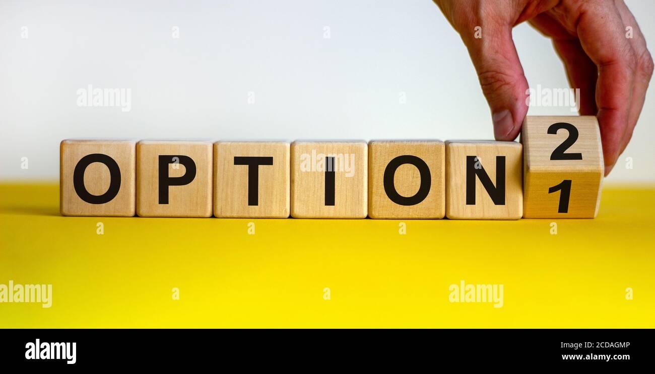 Opción 1 o opción 2. La mano gira un cubo y cambia el número '1' a '2' o viceversa. Palabra opción en cubos de madera. Hermosa mesa amarilla, ba blanca Foto de stock