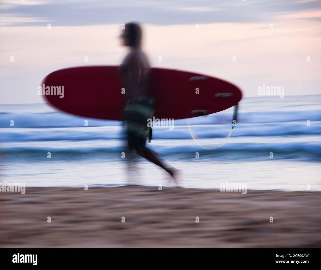 Surfing por la noche al atardecer. Foto de stock