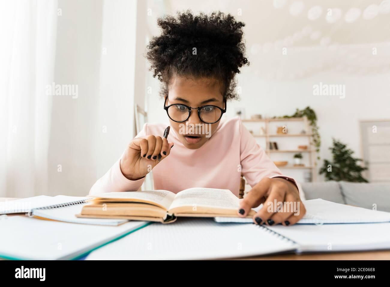 Libro de lectura de la muchacha adolescente africana sorprendida haciendo tareas en el hogar Foto de stock