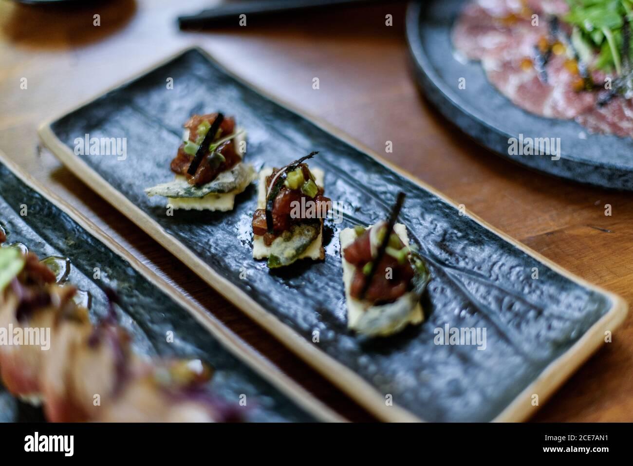 Gran ángulo de delicioso sushi con salmón picado plato sobre mesa en el restaurante Foto de stock