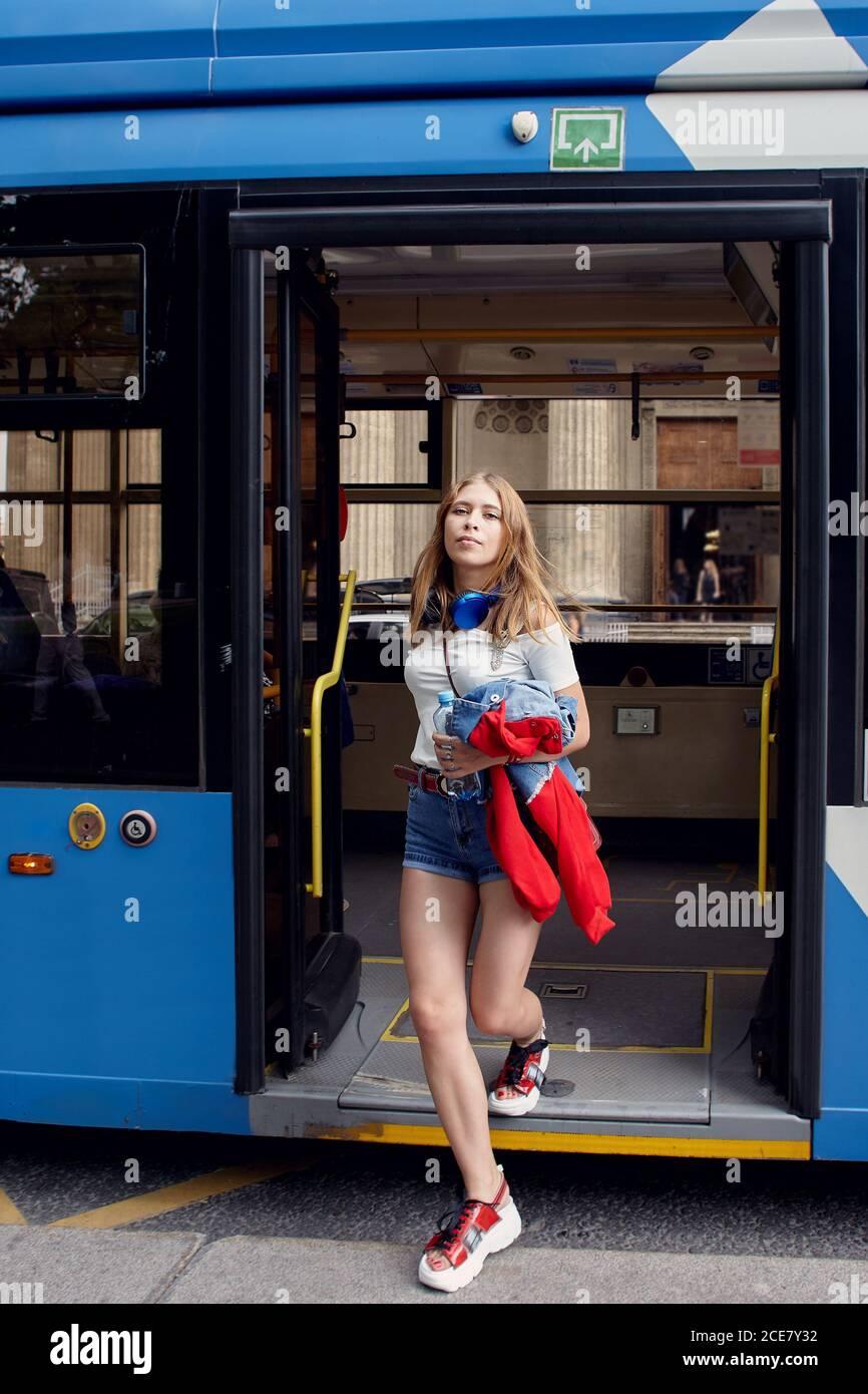Mujer Joven Delgada En El Trolebus Atractiva Dama Caucasica De Unos 25 Anos De Edad En Tela De Moda Con Pantalones Cortos Y Zapatos De Plataforma Se Va A Publico Fotografia De