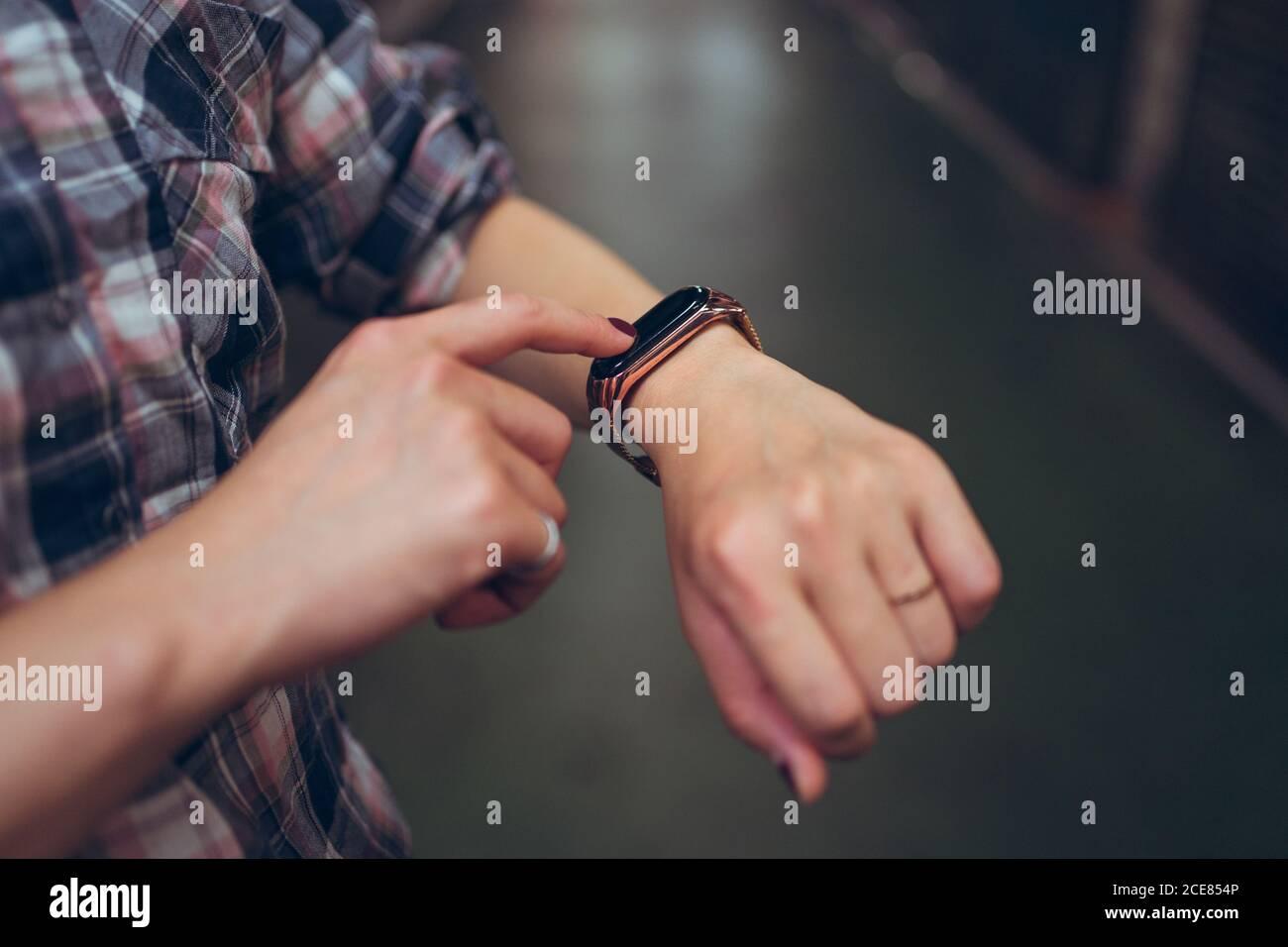 Vista lateral de la cosecha mujer anónima en camisa casual de cuadros comprobación de la hora en la pulsera inteligente Foto de stock