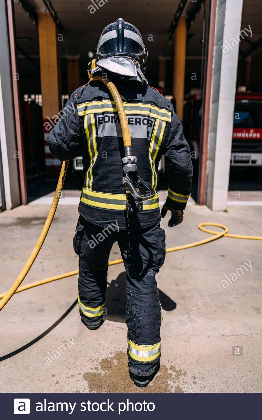 Vista posterior de la cosecha de bomberos anónimos en uniforme de protección con líneas amarillas de pie con manguera larga goteando agua en el pavimento en la luz del día Foto de stock