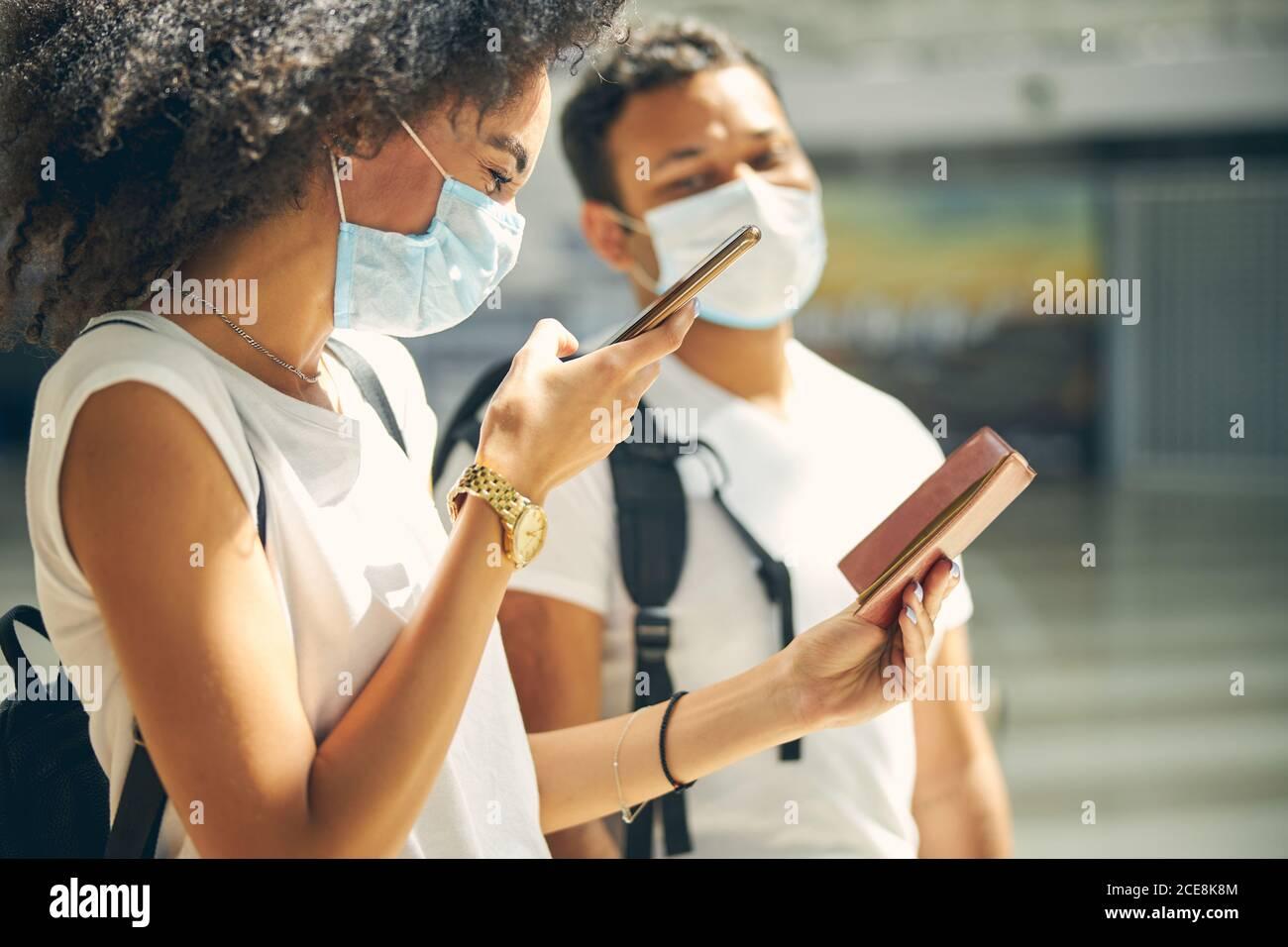 Mujer africana de buen aspecto haciendo fotos de su documento en el móvil teléfono Foto de stock