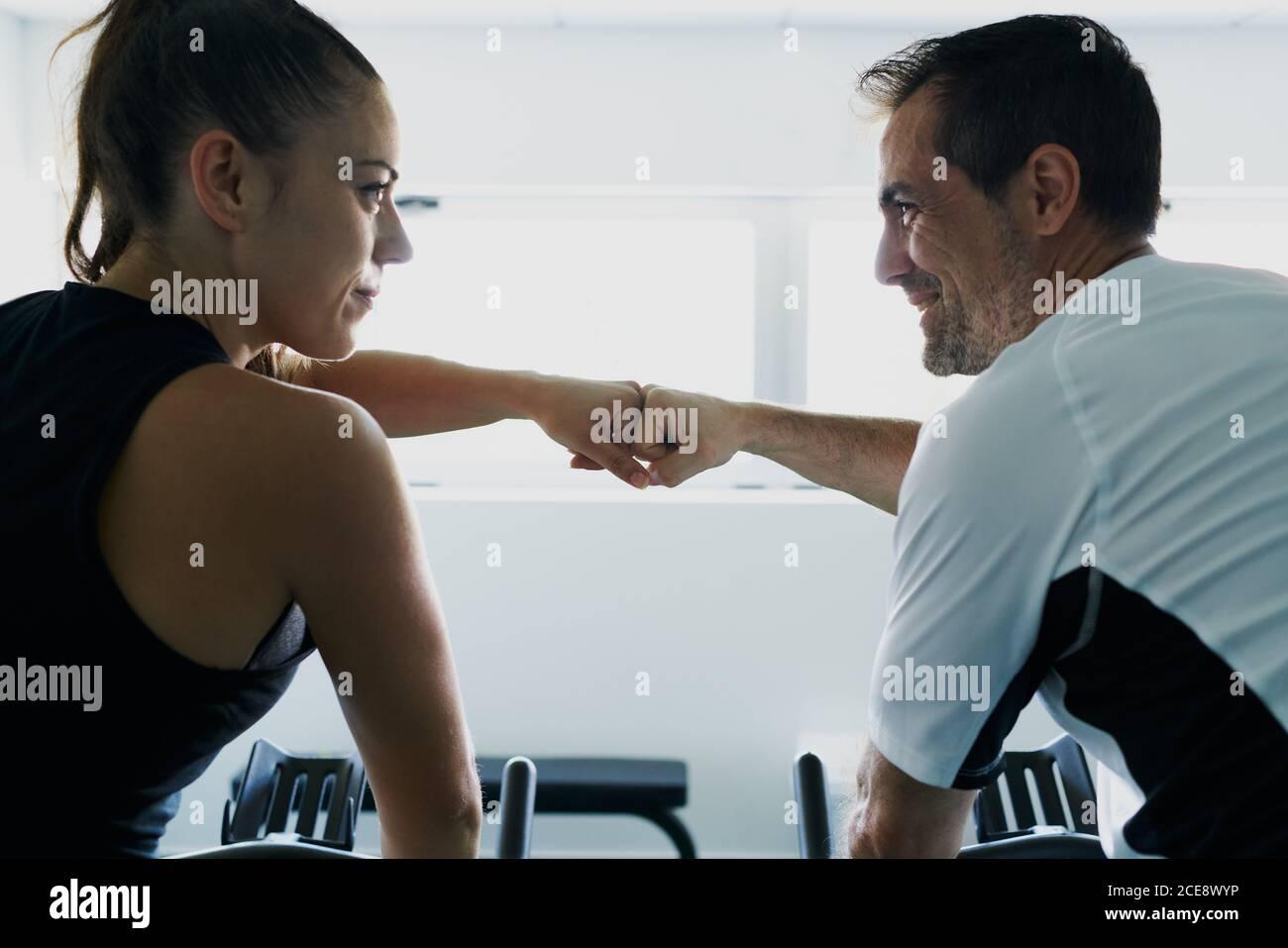 Vista lateral del contenido mujer atleta dando el primer golpe a. instructor masculino personal en el gimnasio moderno Foto de stock