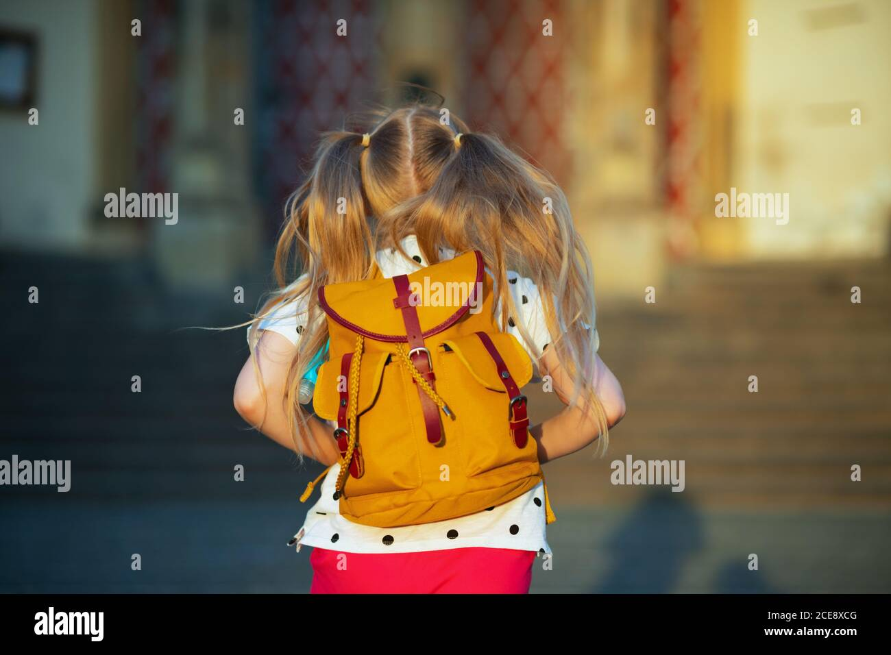 La vida durante la pandemia de covid-19. Visto desde detrás de la niña en blanco polka punto blusa con mochila amarilla yendo de la escuela fuera. Foto de stock