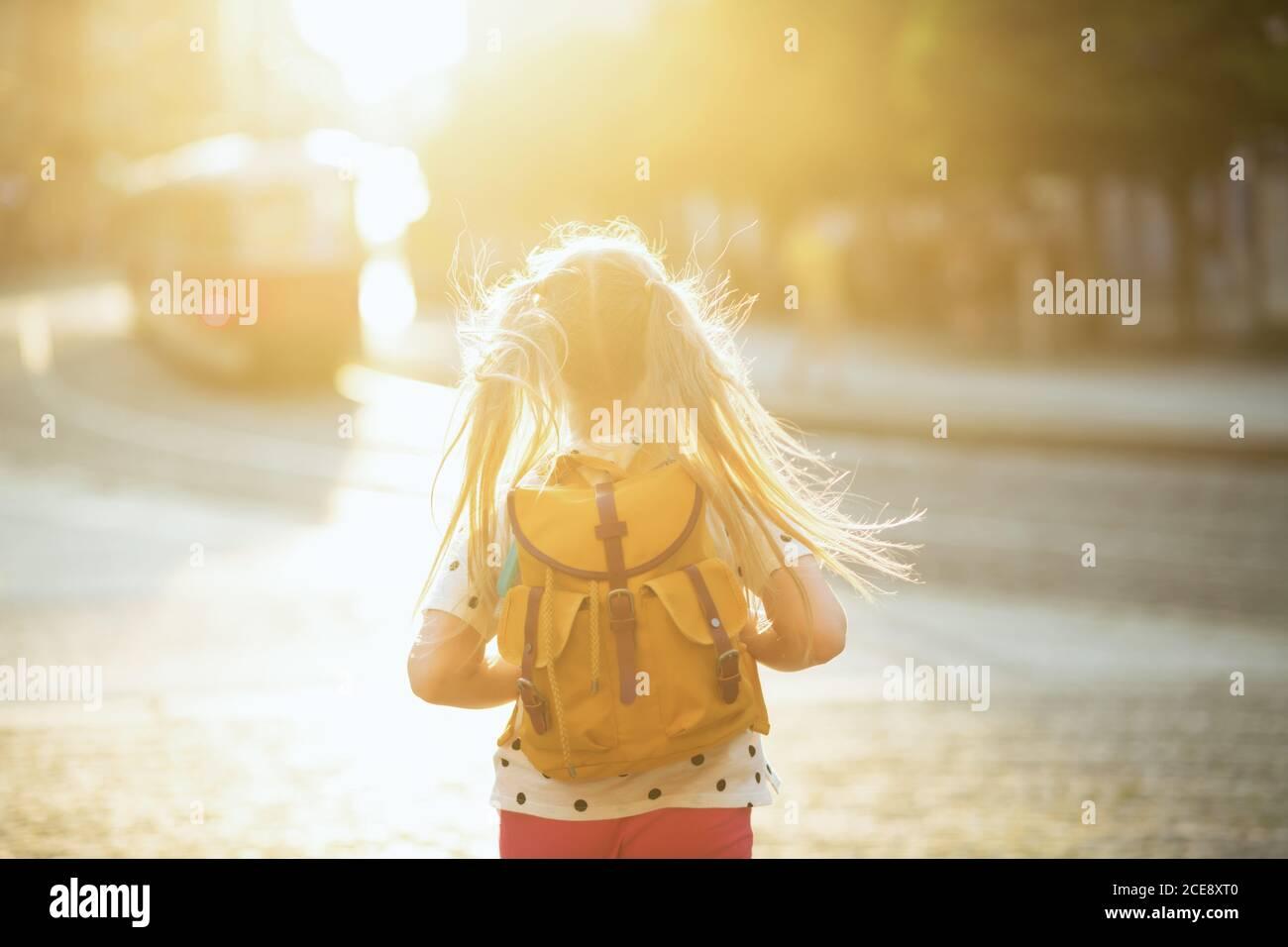 La vida durante la pandemia de covid-19. Visto desde detrás del niño en la blusa blanca de lunares con una mochila amarilla regresando de la escuela al aire libre. Foto de stock