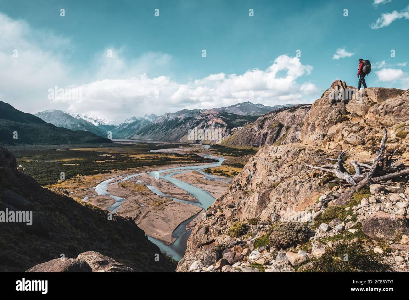 Excursionista en la cima de una montaña admirando un valle con un hermoso río en la Patagonia. Foto de stock