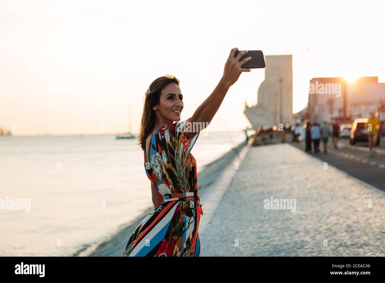 Contenido mujer en vestido usando el teléfono y tomando selfie encendido paseo marítimo en tiempo de puesta de sol Foto de stock
