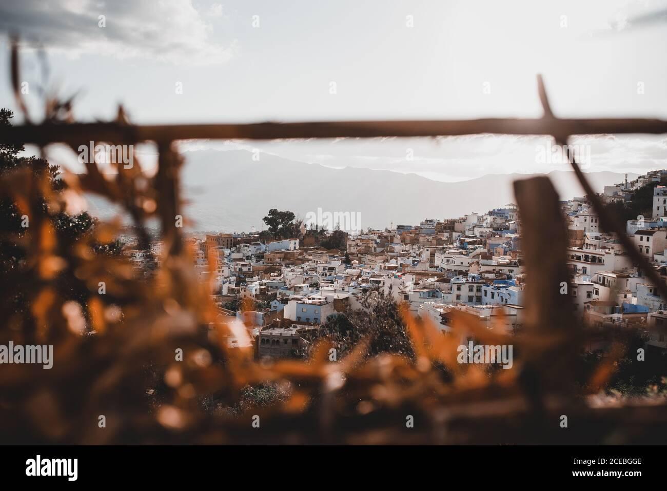 Los edificios de Marruecos se extendieron sobre la colina y iluminados por brillante rayos de sol a través del cielo nublado sobre el fondo de la majestuosa montaña alta Foto de stock