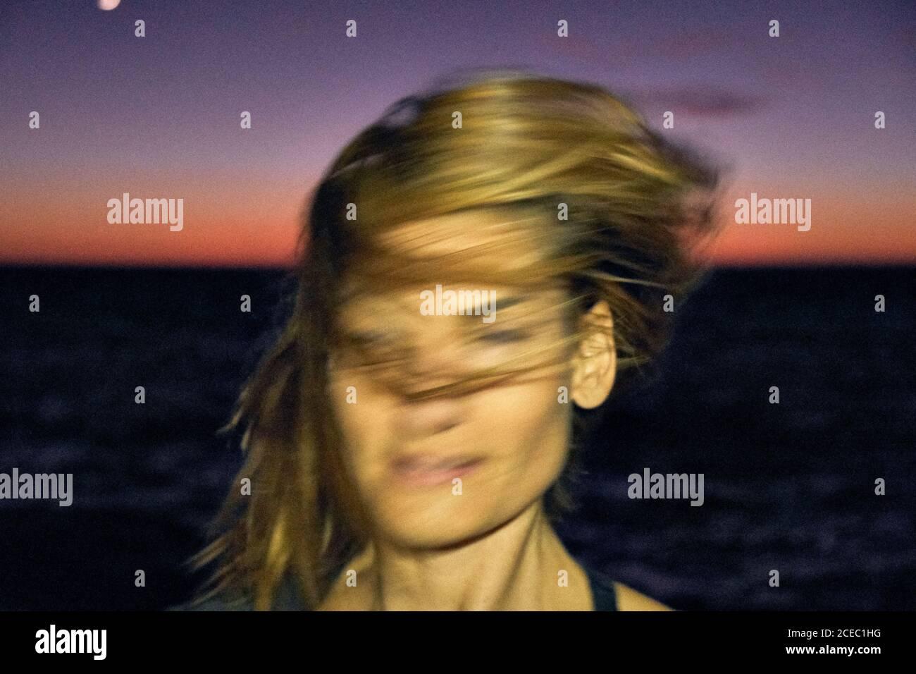 Joven mujer sacudiendo el cabello rubio mientras está de pie contra la noche oscura cielo y mar maravilloso Foto de stock