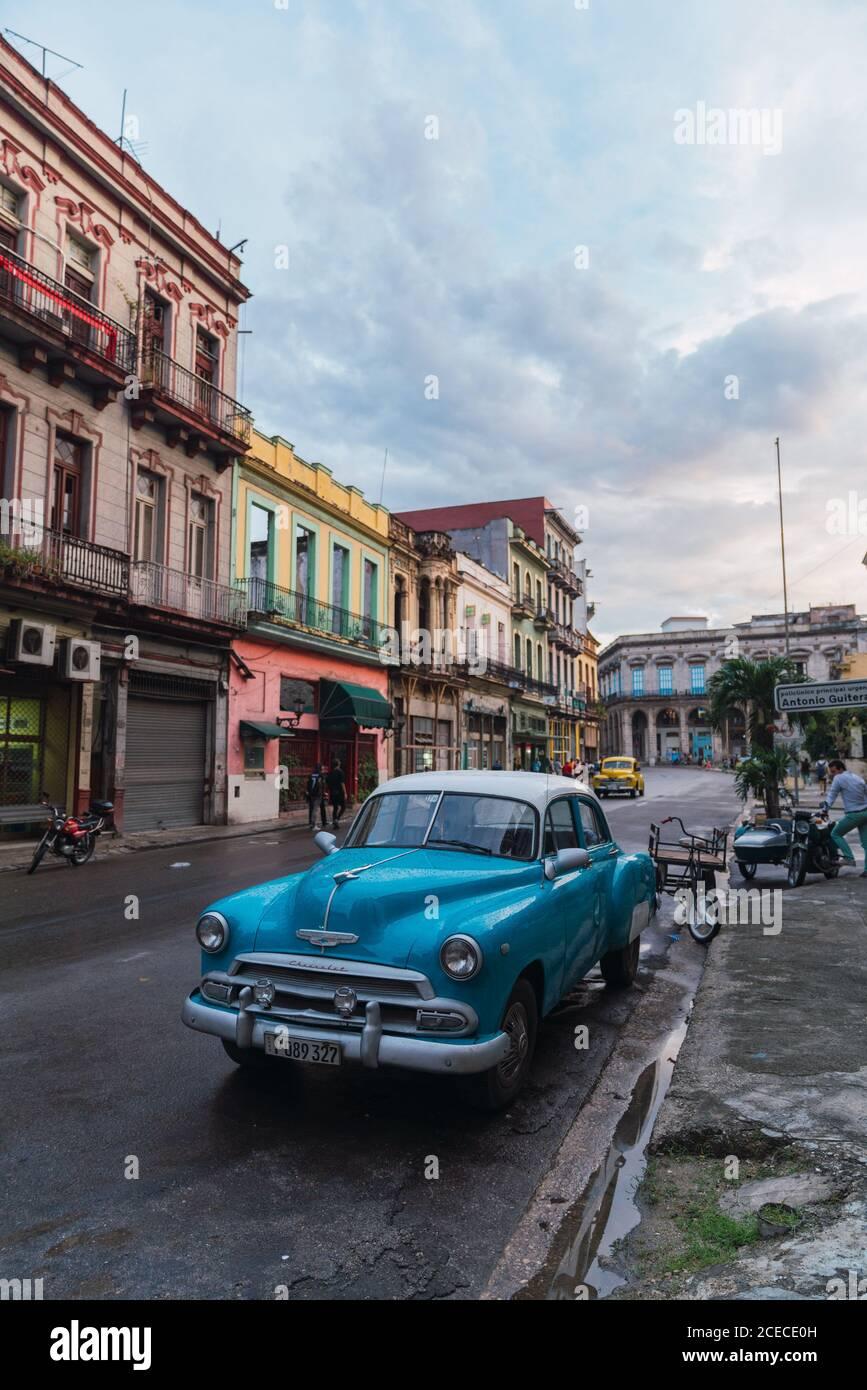LA HABANA, CUBA - 6 DE NOVIEMBRE de 2018: Automóvil de época en la calle cerca de la construcción entre árboles y macho en día soleado en Cuba Foto de stock