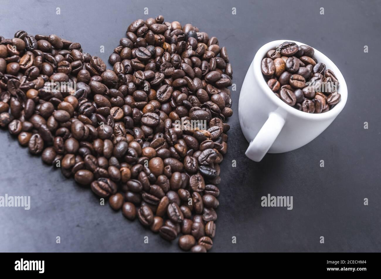Granos de café con taza sobre fondo oscuro, en forma de corazón, primeros planos de vida, planos, estudio interior, me encanta el concepto de café Foto de stock