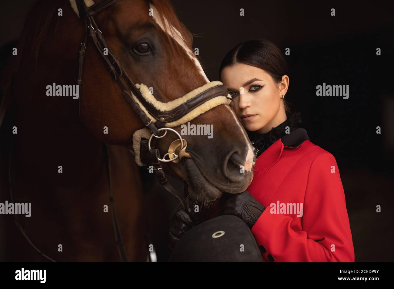 Jinete jinete jinete jinete abraza el caballo marrón con los ojos cerrados. Concepto de animales de amor Foto de stock