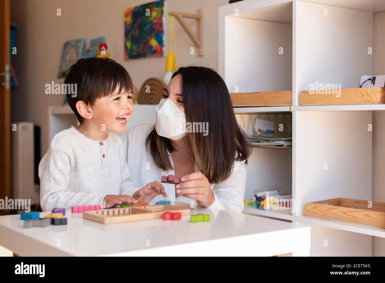 Liltle Preschooler Kid jugando al rompecabezas de madera de tetris con el maestro educador ayuda a usar la máscara para la pandemia del coronavirus. Resolución de problemas en casa. Unidad de aprendizaje Foto de stock