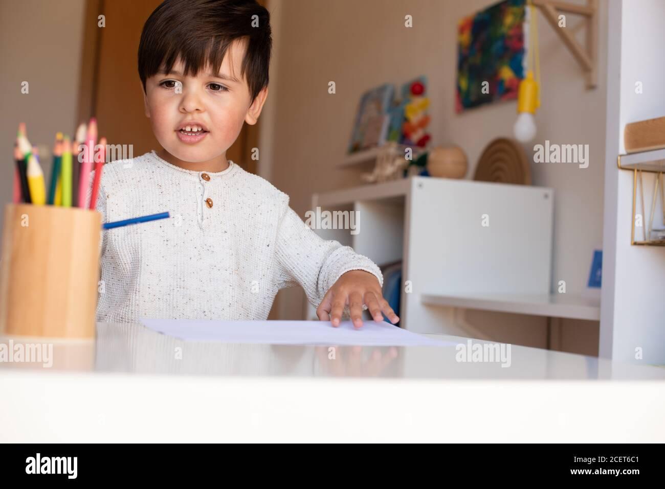 Pequeño niño de preescolar dibujo con lápices de colores. Homeschooling. Comunidad de aprendizaje. Escuela Montessori. Foto de stock