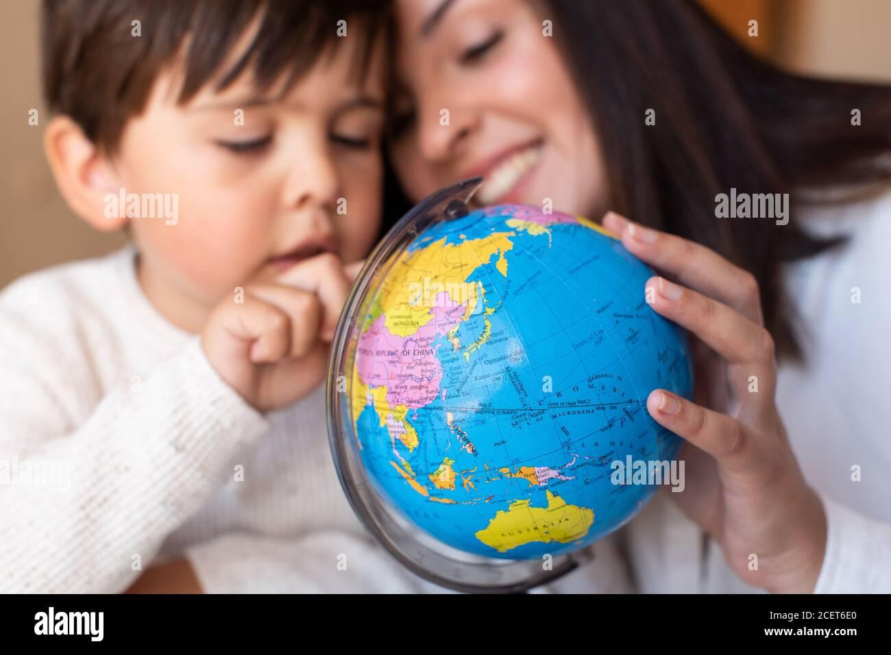 Liltle Preschooler Kid aprendiendo geografía con un mapa del globo y la ayuda del educador del profesor. Resolución de problemas en casa. Comunidad de aprendizaje. Escuela Montessori Foto de stock