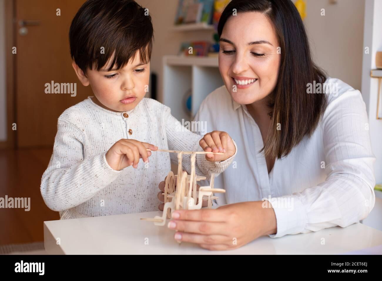 Liltle Preschooler Kid jugando con madera 3d rompecabezas y maestro educador ayuda. Resolución de problemas en casa. Comunidad de aprendizaje. Escuela Montessori Foto de stock