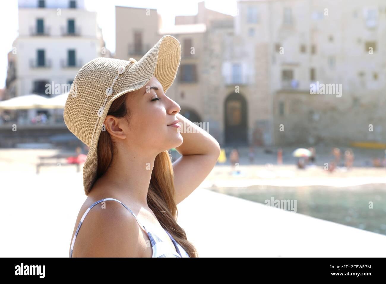 Cerca de una joven hermosa mujer con sombrero disfrutando del sol en la playa. Vacaciones relajantes tomando el sol en Cefalu, Sicilia. Foto de stock