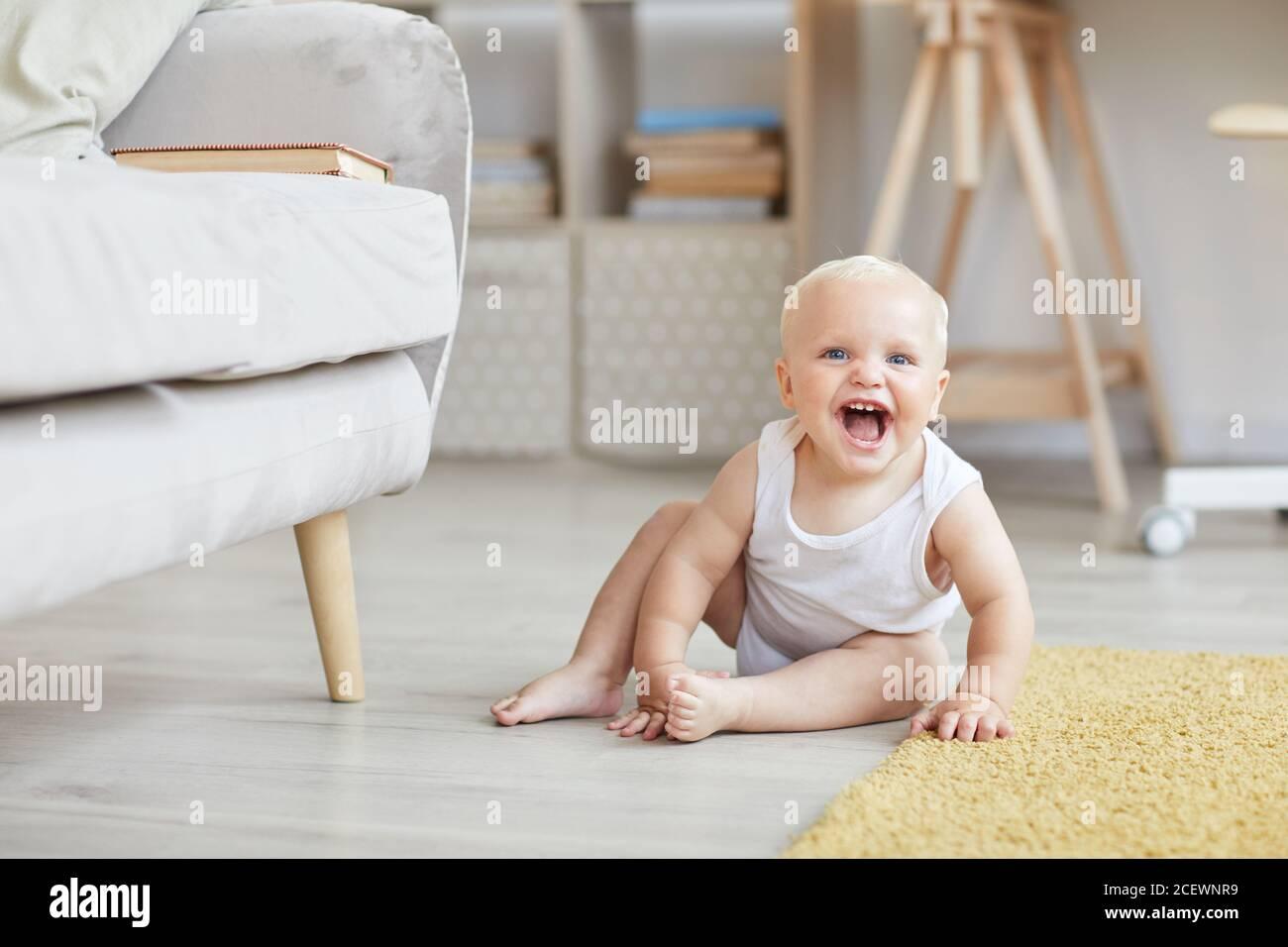 Tiro horizontal de feliz bebé juguetón sentado en el suelo en la sala de estar jugando y riendo, copiar espacio Foto de stock
