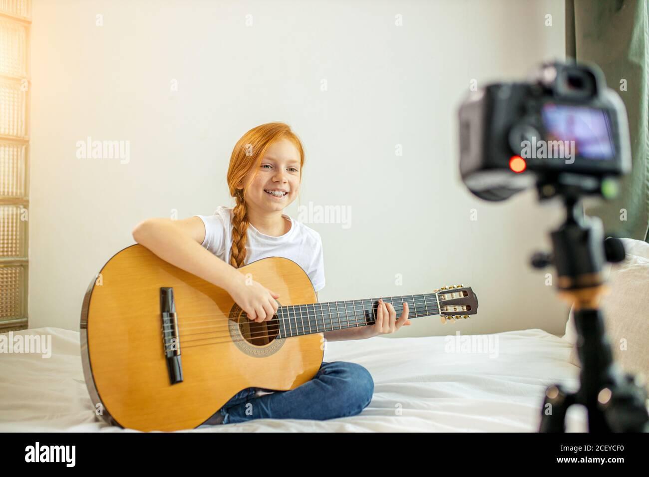 retrato de la hermosa niña caucásica blogger tocando la guitarra en la cámara. adorable chica sentada mostrando, realizando nueva melodía para los suscriptores. vl Foto de stock