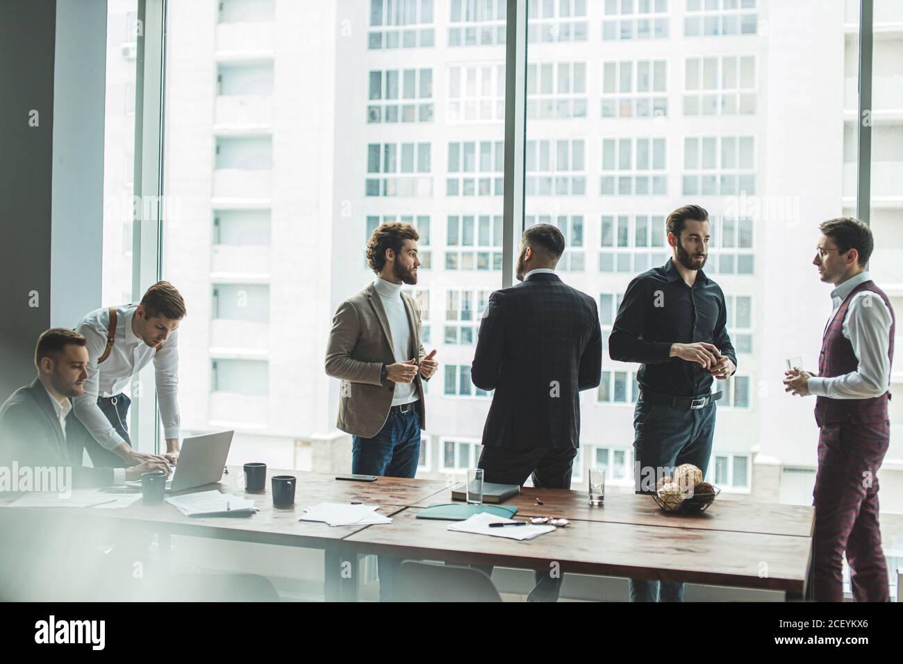 hombres de negocios compañeros de trabajo en la oficina, la tripulación de negocios consistía en hombres jóvenes líderes tienen tiempo de lluvia de ideas, discutir, crear y desarrollar nuevos proje de negocios Foto de stock