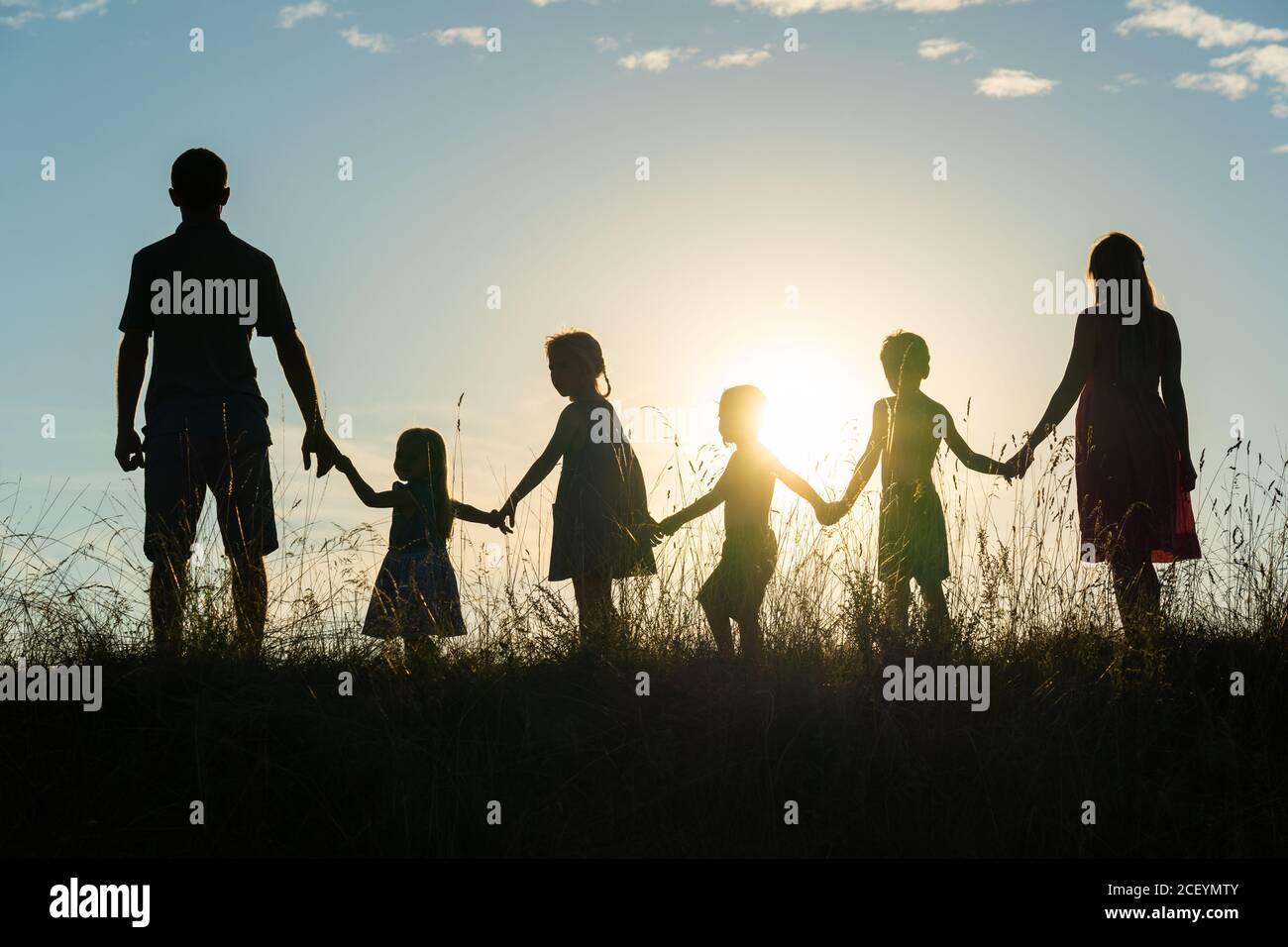 Silueta de una familia grande feliz al atardecer. Foto de stock