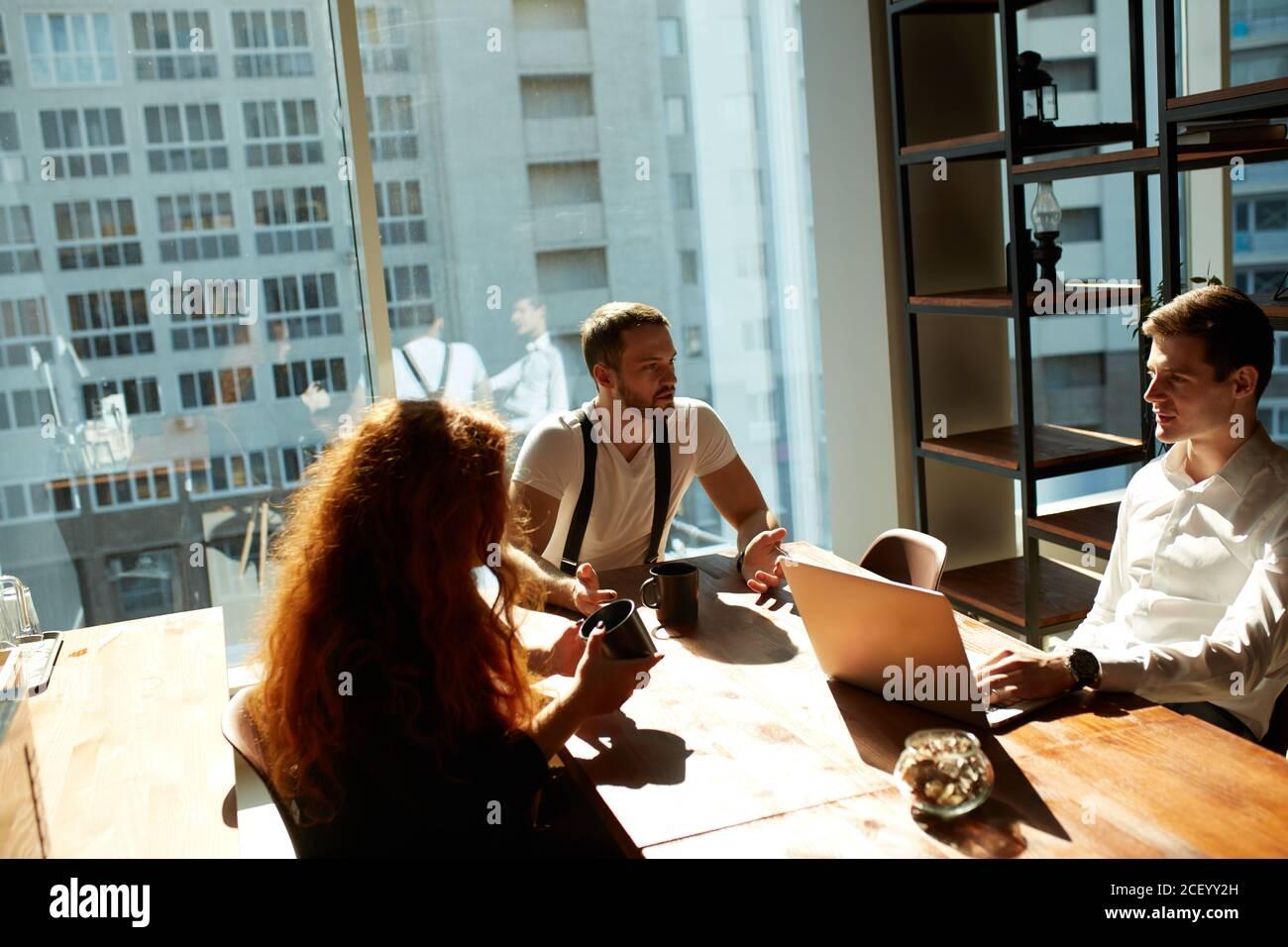 Empleados que tienen una discusión durante una pausa para tomar café en la oficina. Relaciones complicadas y conflictos en el lugar de trabajo. 2 hombres teniendo una conversación acalorada a Foto de stock
