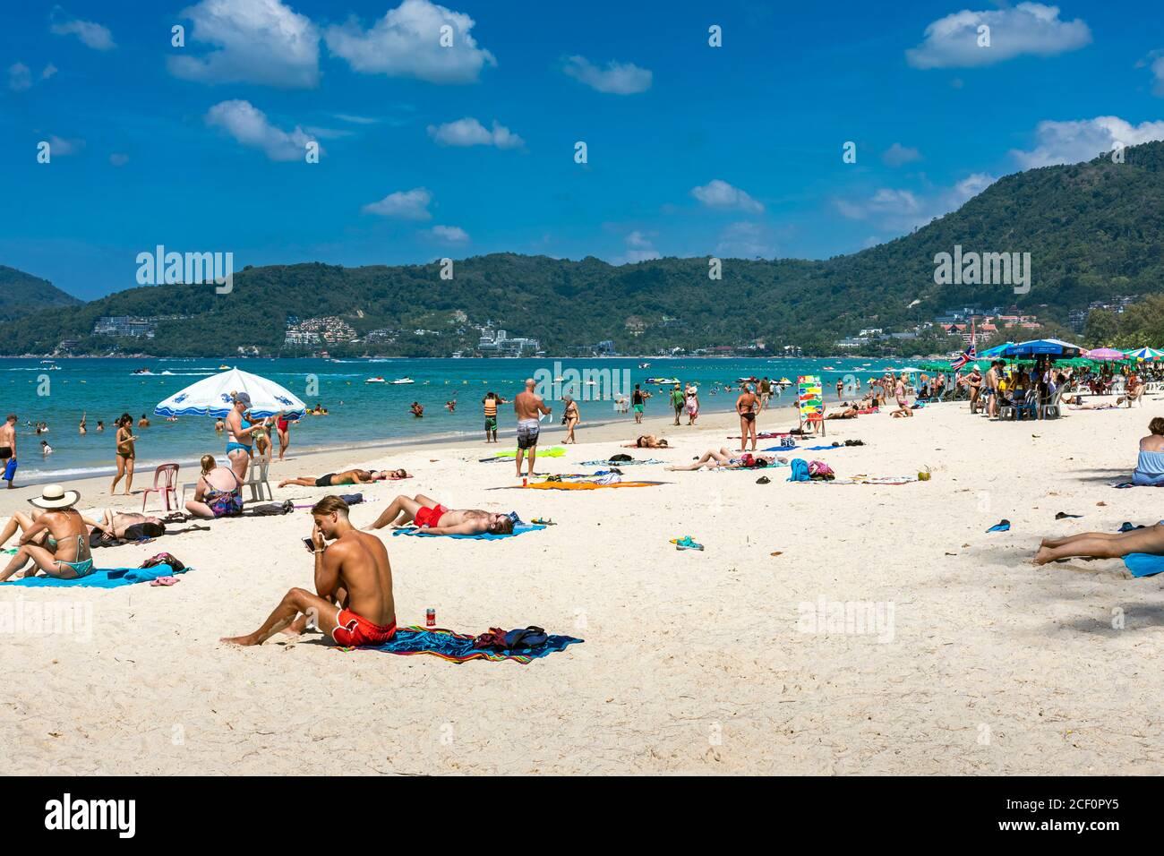 Turistas tomando sol en la playa, Patong, Phuket, Tailandia Foto de stock