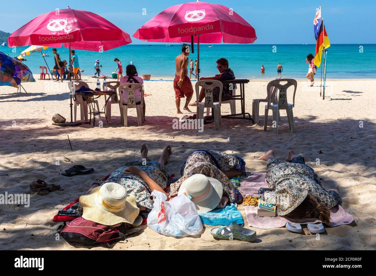 Turistas durmiendo en la playa, Patong, Phuket, Tailandia Foto de stock