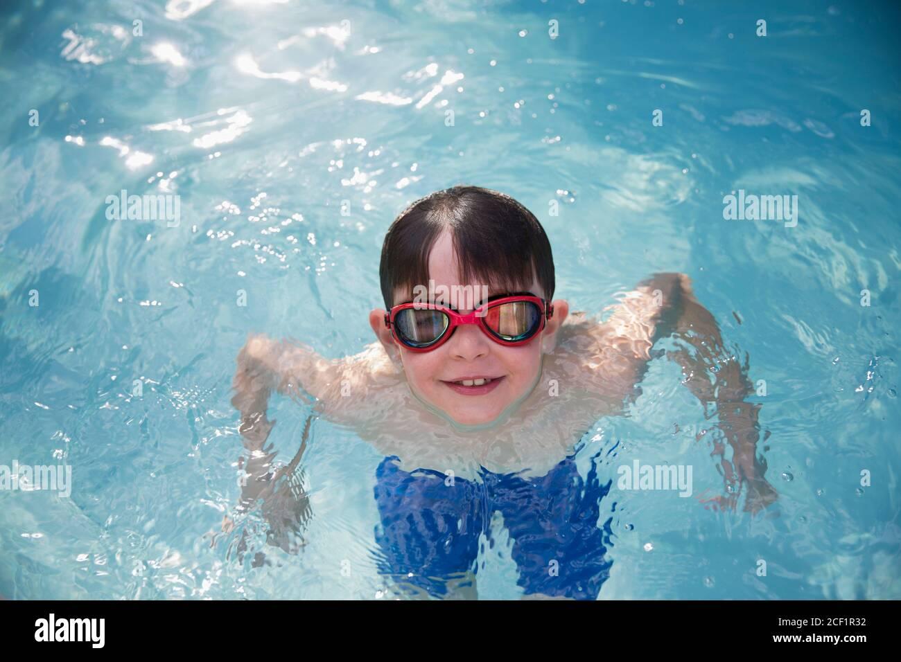 Retrato sonriente niño en gafas de natación en la piscina soleada Foto de stock
